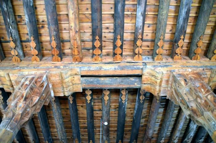 Ozdobne kapitele drewnianych kolumn oraz belkowanie dachu