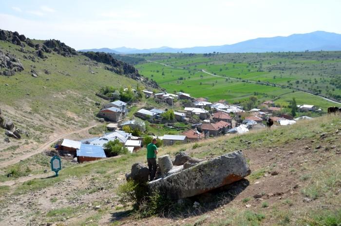 Monument hetycki w Fasıllar - w tle wieś, a na monumencie przedstawiciel redakcji TwS daje wyobrażenie o skali monolitu
